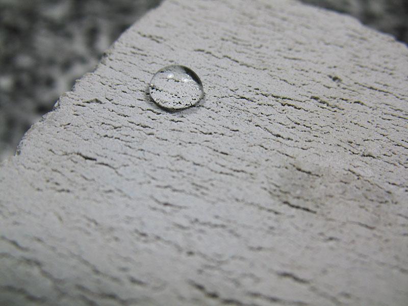 waterdruppel op een zeer poreuze steen die is behandeld met nanocoating