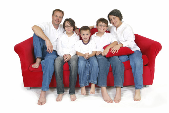Red sofa with happy family, including mum.