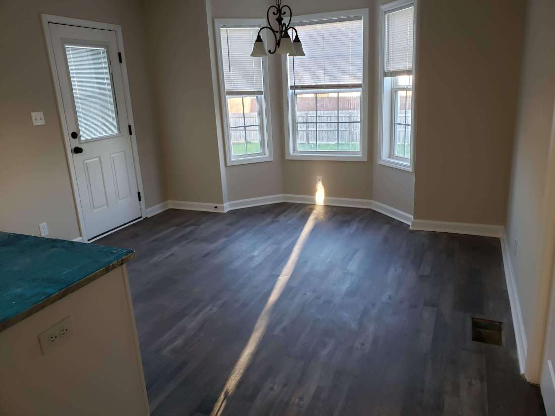 A newly mopped and clean laminate vinyl plank (lvp) floor overlooking new windows