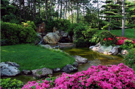A landscape garden, with pink flowers and a stream.