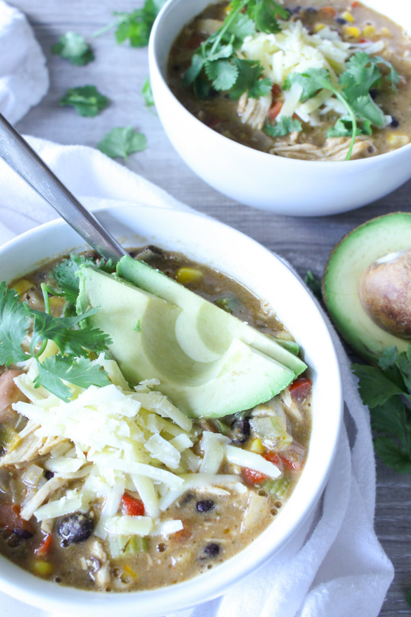 Angled view of 2 bowls of chicken chili in white bowls topped with shredded cheese, avocado, and cilantro
