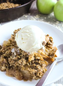 45 degree angle view of one serving of apple crisp topped with vanilla ice cream