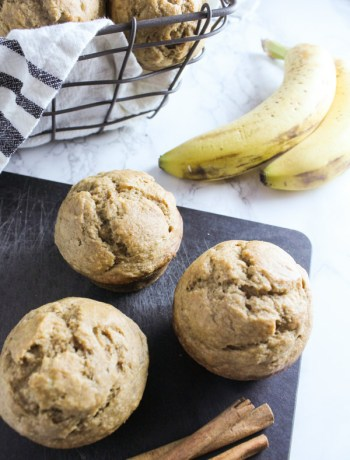 Whole wheat banana bread muffins on cutting board with filled basket behind