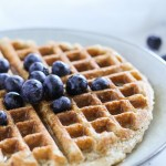 close up side angle view of waffle with blueberries and syrup