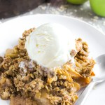 side view of apple crisp on plate with vanilla ice cream