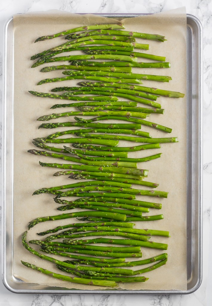 overhead view of raw asparagus spears on baking sheet