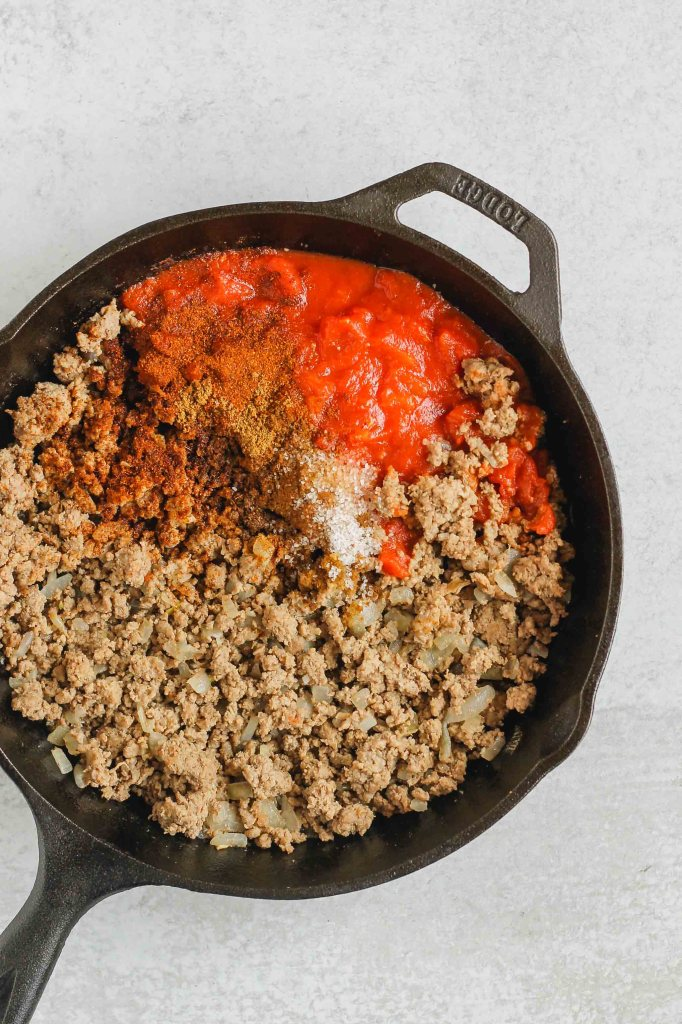 overhead view of cooked ground beef, seasoning, and tomatoes in cast iron skillet before being mixed together