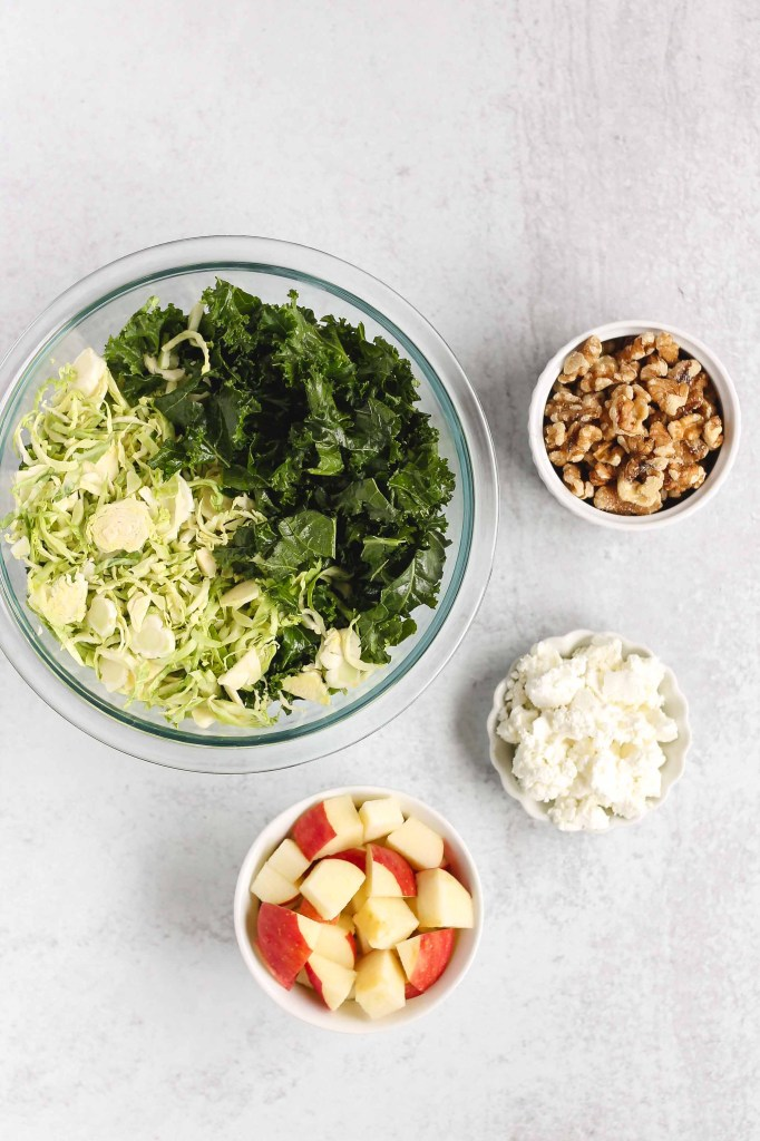 overhead view of apples, goat cheese, walnuts, and Brussels sprouts and kale all in separate bowls