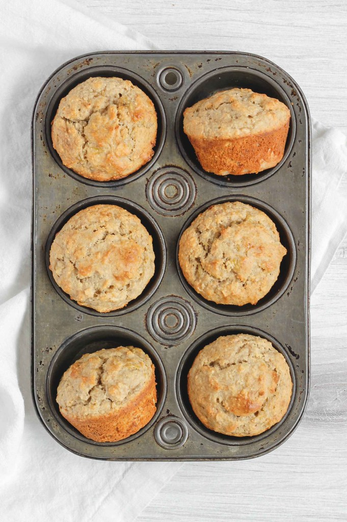 overhead view of banana muffins in and antique tin muffin pan