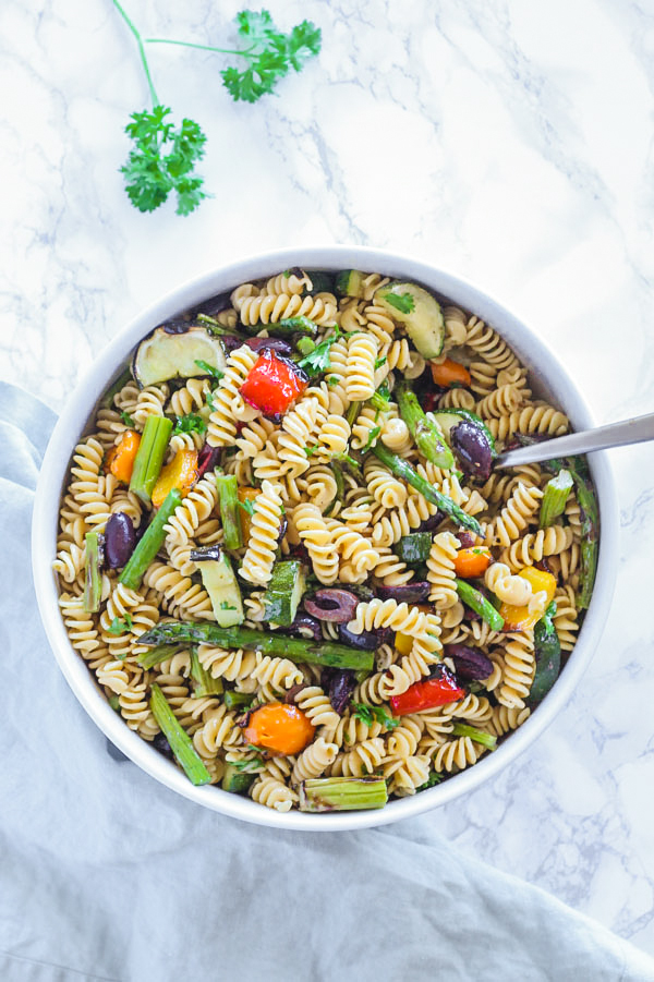 overhead view of grilled vegetable pasta salad in large round serving bowl with spoon