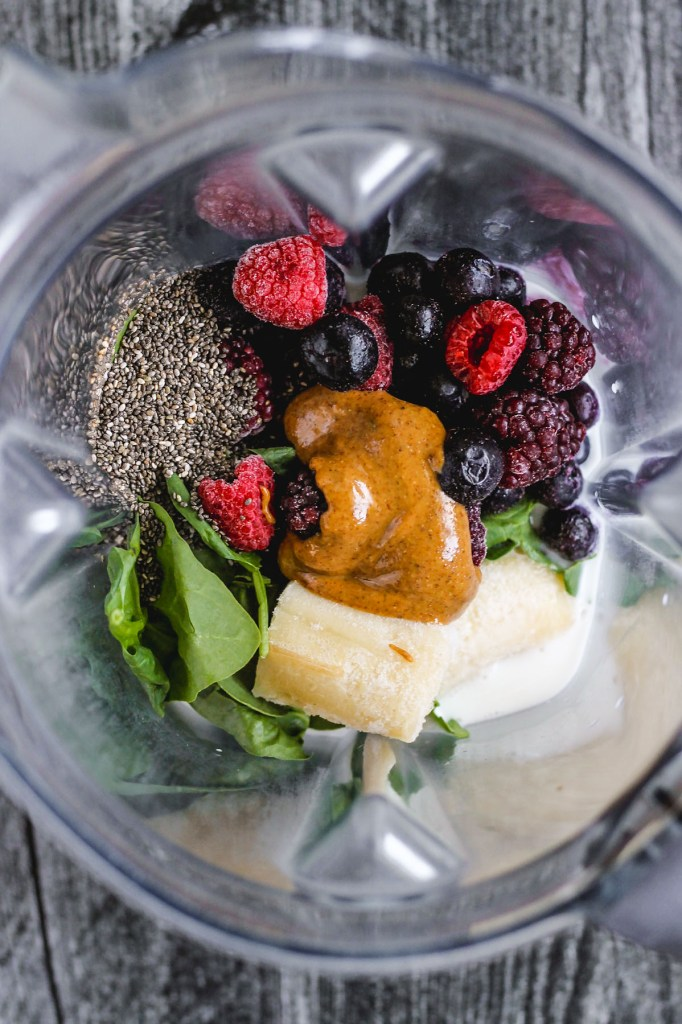 view of chia seeds, spinach, banana, almond butter, frozen mixed berries, and almond milk in blender before being blended