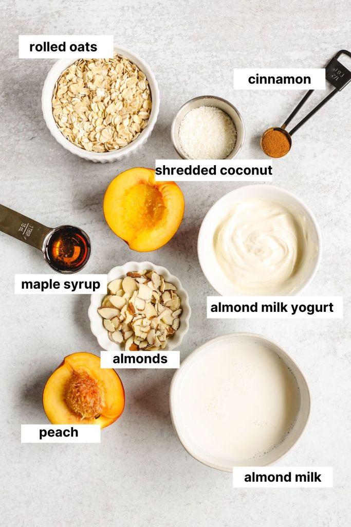 ingredients needed to make peaches and cream overnight oats (oats, cinnamon, shredded coconut, maple syrup, almonds, almond milk yogurt, peach, almond milk).