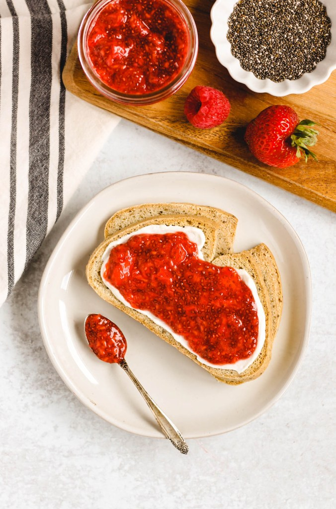 overhead view of two slices of toast on a plate with cream cheese and berry chia jam spread on toast