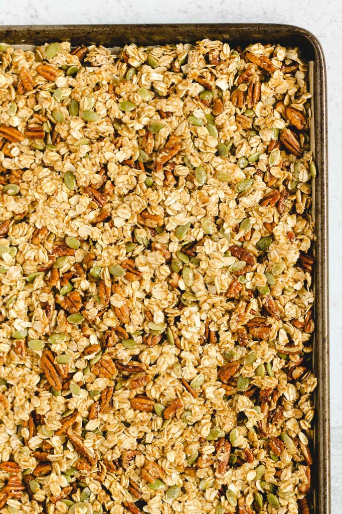 overhead view of pumpkin granola on baking sheet before it has been cooked