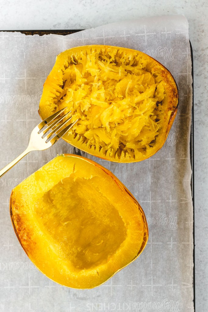 "2 roasted spaghetti squash halves - one half has the the squash scraped with a fork showing the spaghetti squash ""noodles""."
