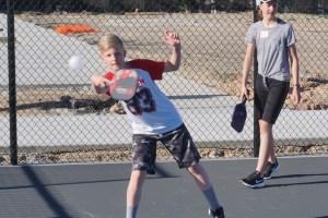 Boy returning ball with paddle.