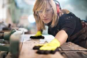 Female craftperson with protective equipment working with planks in workshop. She is making furniture parts.