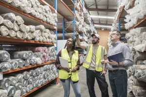 Mid adult man in hi vis pointing to carpets on shelves and discussing with two colleagues