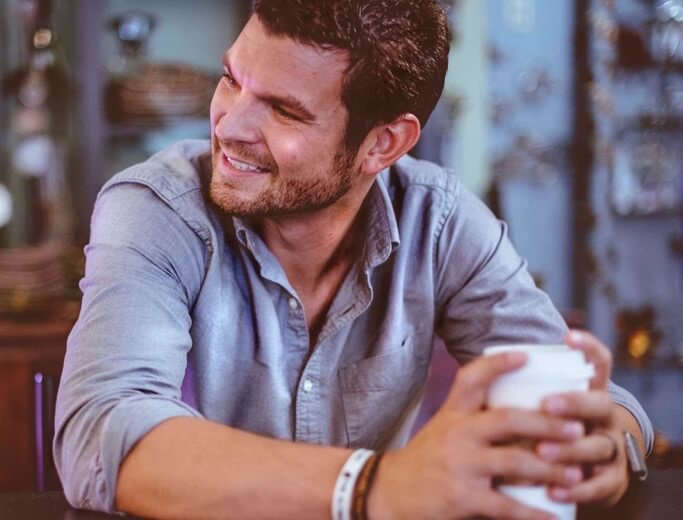 Photo of a man smiling with a cup of coffee