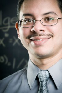Male hispanic educator in front of blackboard