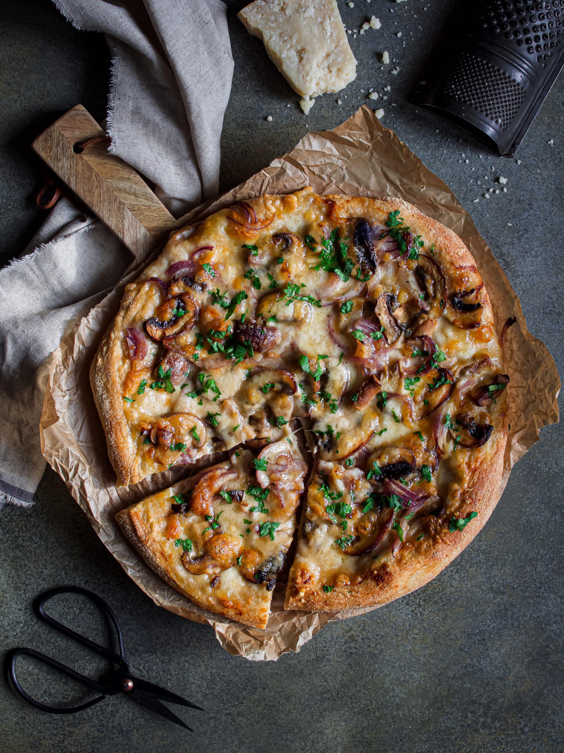 photo d'une pizza aux trois fromages avec des champignons et oignons caramélisés