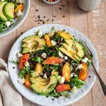 Une assiette avec la salade de lentilles, orange et avocat, et une autre dans le coin, un pot de vinaigrette et un petit pot de poivre