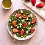 fond rose pâle avec assiette blanche contenant une salade de roquette, quinoa, fraises, petits pois et asperges avec des morceaux de fromage de chèvre frais et de la menthe, un petit pot de vinaigrette et une planche blanche avec des fraises entières dessus