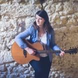 Clem jouant de la guitare adossée à un mur de pierre