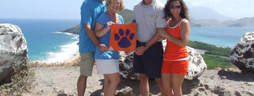 West Indies - Brad '82 and Leigh Anne Whitlock '83 Hoover, and Chris '88 and Heather Whitlock posed with their Tiger Rag in St. Kitts.