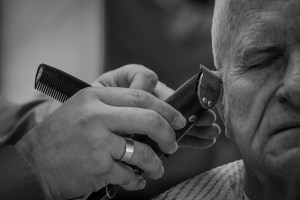Mike Laye puts the finishing touches on a haircut for long-time client Tom Campbell at the Clemson House Barber Shop, Jan. 9, 2015. The small barbershop, located in one of Clemson's iconic student dormitories, has been in operation for 64 years. Laye is the third generation of his family to cut hair there, as his father and grandfather did before him. (Photo by Ken Scar)