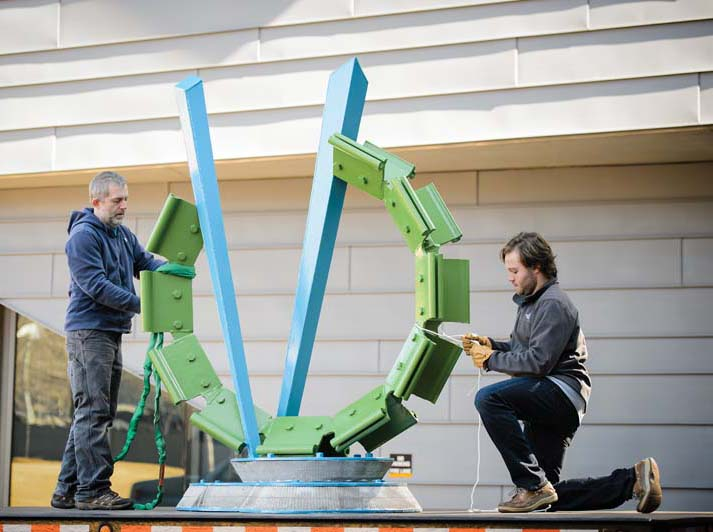 Professor Joey Manson and visual arts major David Lamm installing Manson's sculpture.