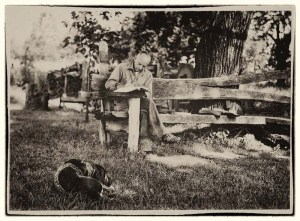 "Aldo Leopold, writing outside ""The Shack"" with his dog Flick."