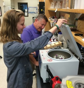 Marissa Pierson, a master's student, closes the lid on a centrifuge while workinh gin a Clemson lab with Professor Ken Marcus.