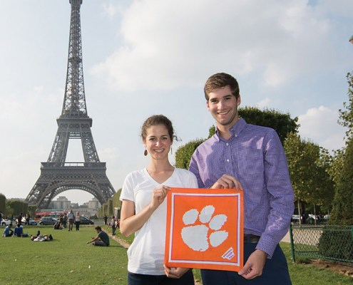 France Sara Webb '14 and Alex Devon '14 show Clemson pride in front of the Eiffel Tower while visiting Paris.