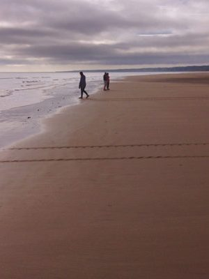 Clemson students walk along the hallowed ground of Omaha Beach at low tide.