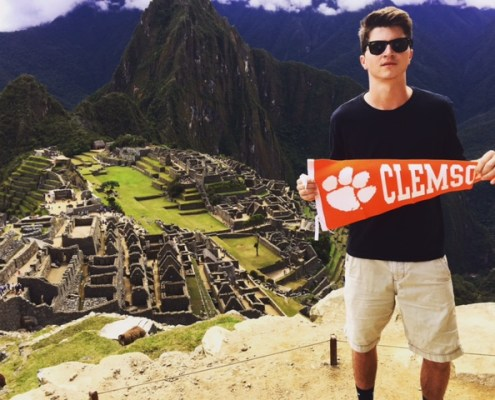 Nathan Creel '19 stands with his Clemson pennant over Machu Picchu in Peru.