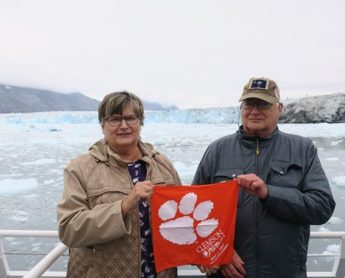 Kathy '75 and Maynard '70 Davis wave their Tiger Rag over the Columbia Glacier on Prince William Sound in Alaska.