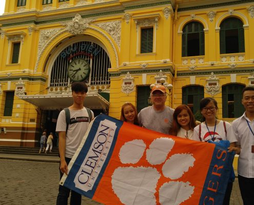 Floyd Harris '78 traveled throughout Vietnam visiting children's schools and orphanages in preparation for teaching English as a second language. He shared his Tiger pride with local university students in front of the Saigon Central Post Office in Ho Chi Minh City.