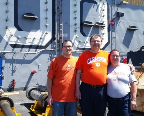 Ensign Daniel Minnick stood with his parents, Mike Minnick '81, Ph.D. '84 and Anne Minnick '83, aboard the U.S.S. Nimitz in Bremerton, Washington, shortly before its current deployment to the Persian Gulf.