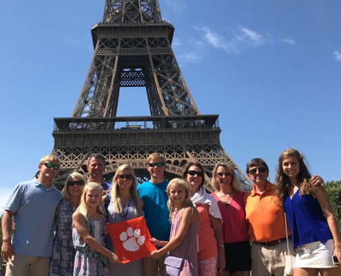 William Stevens '67 and granddaughter Lucy Stevens '18 pose with the rest of their family at the Eiffel Tower, celebrating William's 50th wedding anniversary with wife Linda.