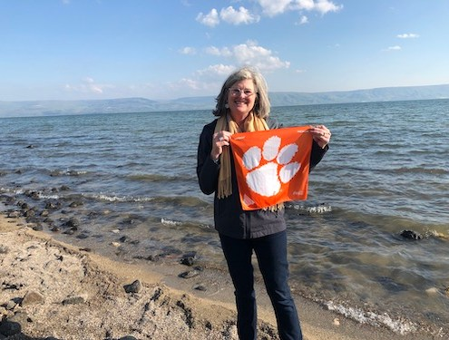 "Israel: Kay Lindsay Sporrer '82 on the shores of the Sea of Galilee in Tiberias. ""This sea is mentioned many times in the Bible, but probably the most well-known is when Jesus and Peter walked on water."""