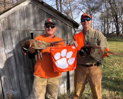 "Iowa: George McCutchen '94, right, traveled to Iowa to hunt pheasants with his friend Jason Webb, ""who operates a large trucking company all over the U.S. from Des Moines — educating all of Iowa on the reach and pride of Clemson!"""