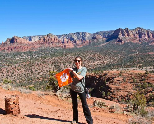 """Arizona: Jenny Litzenberger '11 planned an extensive hiking and driving trip to Colorado, Utah and Arizona at the end of February 2021. """"This picture was taken in Sedona, Arizona on the Cathedral Rock Trail,"""" she wrote. """"It is only listed at 0.7 miles, but it is extremely steep and difficult. There are 'cairns' throughout to guide you along the trail, since it is sometimes difficult to see a path when you are hiking on rock faces. A cairn is the basket of rocks in the picture, but they may also be in a stacked, tower-like rock structure."""""""