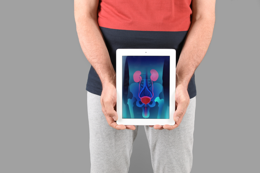 man holding tablet in front of waist with prostate organs