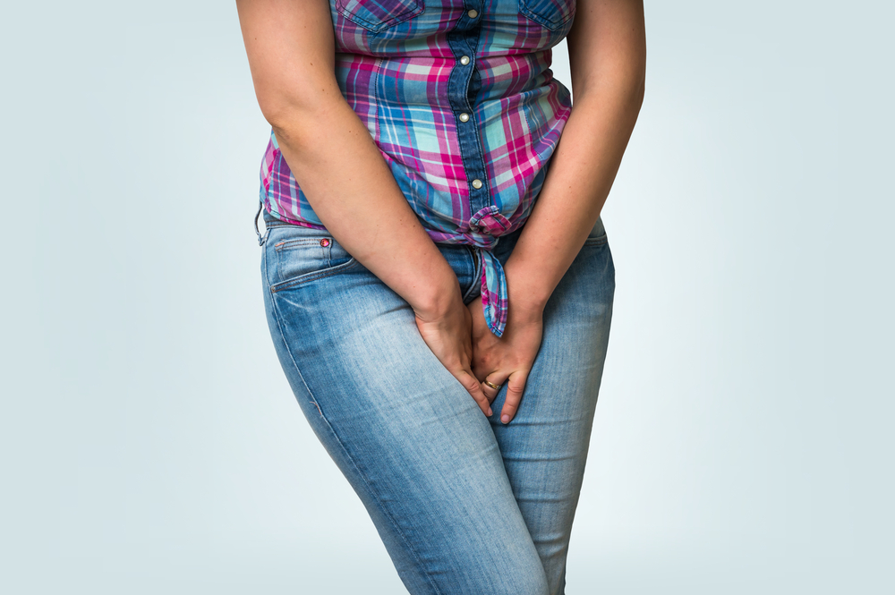 Woman with hands holding her crotch from urinary problem