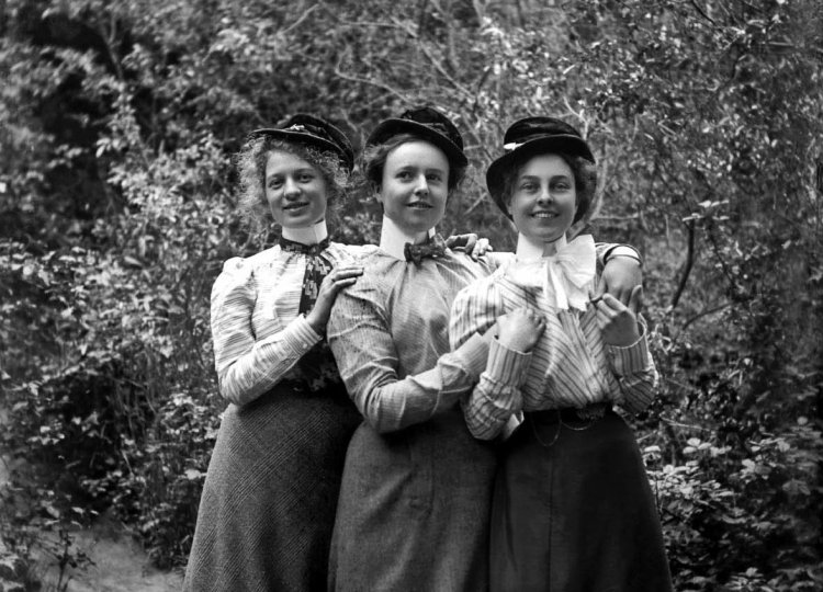 Three women UC Berkeley students wearing senior plug hats c1900
