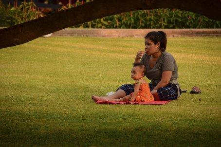 Bangkok Santi Chai Prakarn Park mamma e bimba si rilassano nell'erba