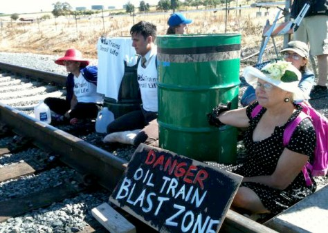 Three Seattle area resident blockade train tracks at the Tesoro's Anacortes Refinery. Photo credit: @SeattleActivist