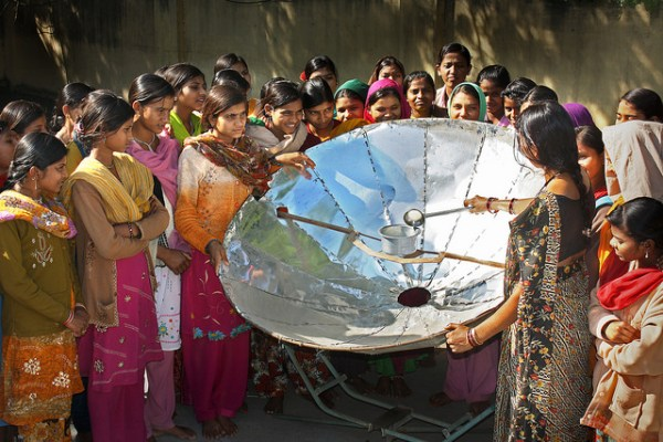 """""""Women learning how to use a solar cooker. Solar cookers can help to reduce deforestation and carbon production bringing cleaner air locally as well as lower carbon globally."""" Climate Outreach Climate Visuals Portal"""