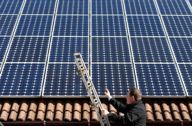 A man in Germany examines the solar panels on his roof, making power he can resell at an excellent financial return. Germany recently installed more solar cells in a single month than the United States did in all that year. (Reuters)